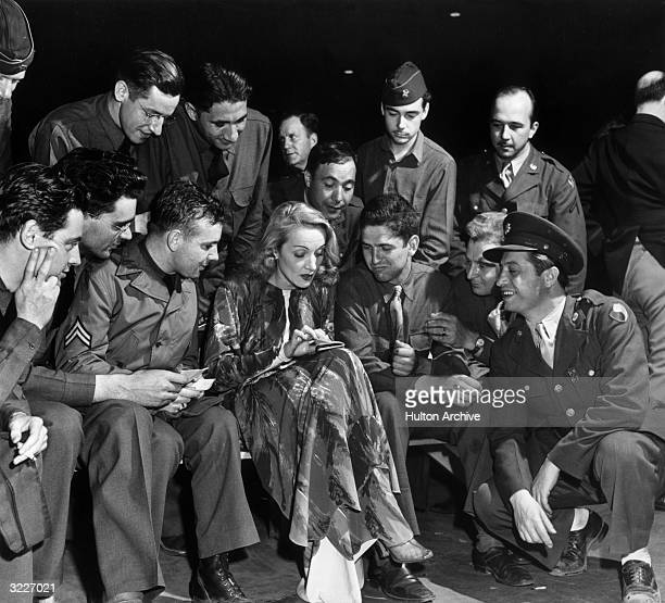 German-born actor Marlene Dietrich sits and looks through a notebook, surrounded by a group of American servicemen on her USO visit to Camp Meade,...