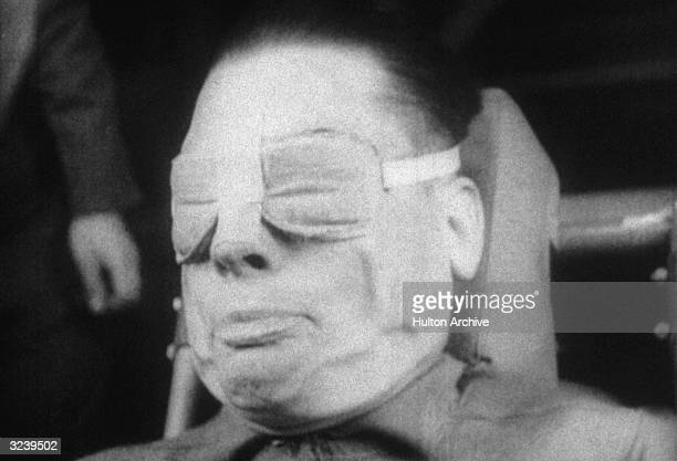 Headshot of a US military test subject undergoing GForce testing while seated and wearing padded eye protection His face is distorted with his mouth...