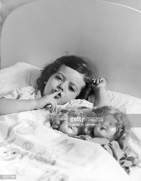 Headshot of a young girl laying in bed with two baby dolls under the covers making a silencing gesture to the camera with her finger