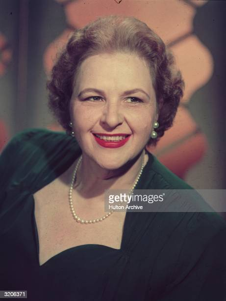 Headshot portrait of American vocalist Kate Smith smiling while wearing a dark dress and a string of pearls