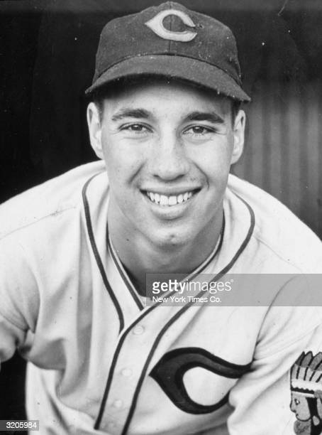 Headshot portrait of Cleveland Indians pitcher Bob Feller smiling in his uniform and cap
