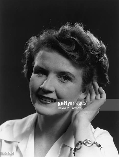 Headshot studio portrait of a woman cupping her hand to her ear 1940s