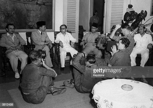 Indonesian President Dr Sukarno and members of his government face British cameramen after a cabinet meeting held in the President's Batavia residence