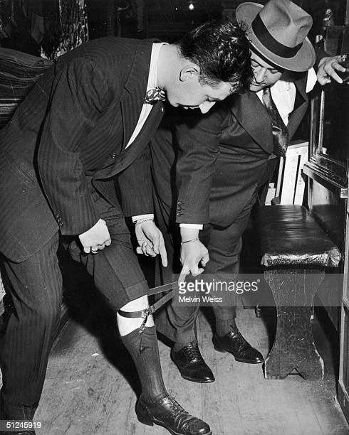 Circa 1945, Jack Leonard tries on a garter meant for a man twice his size, in the Fat Mens' Shop in New York.
