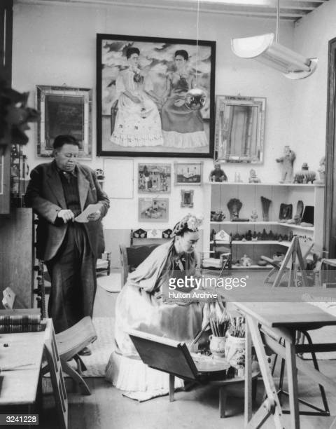 Married Mexican artists Diego Rivera and Frida Kahlo read and work in a studio Kahlo's selfportrait 'The Two Fridas' hangs in the background with...
