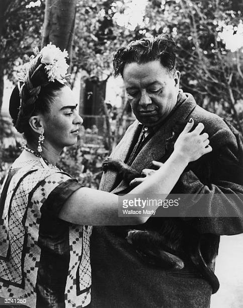 Mexican artist Frida Kahlo pets a monkey possibly FulangChang clinging to the jacket of her husband Mexican artist Diego Rivera