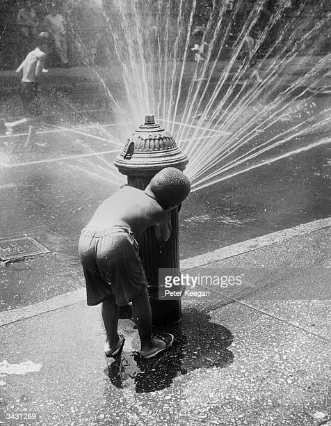 New York children cooling off under the spray of a fire hydrant during a heat wave