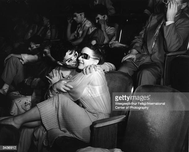 **NOT TO BE USED FOR POSTCARDS** Two lovers at the Palace Theatre kissing in the front row Taken with infrared negative Photo by Weegee/International...