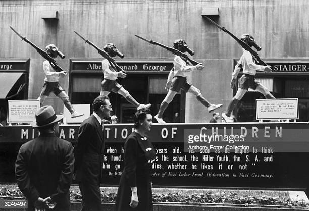 People view an anti-Nazi display with statues of young boys wearing shorts, armbands, gas masks and carrying rifles, Rockefeller Center, New York...