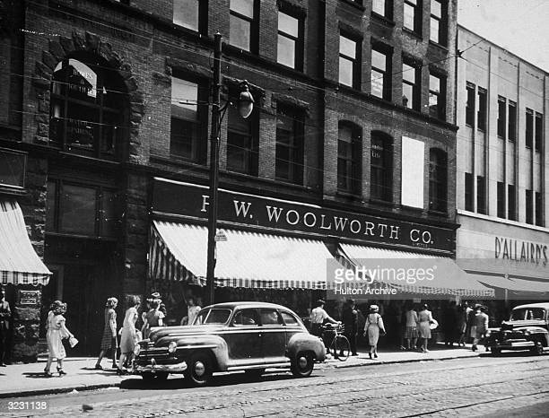 People walk on the sidewalk in front of the F W Woolworth Company department store on a downtown street in Halifax Nova Scotia An automobile is...