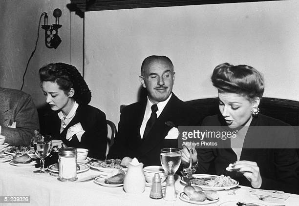 Circa 1945 Polish born American film executive and cofounder of Warner Brothers Jack Warner sitting down to dinner between the American actresses...