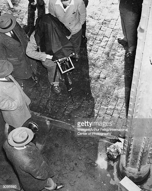 Polish born American photographer Weegee photographs a human head at the scene of a murder Photo by Weegee/International Center of Photography/Getty...