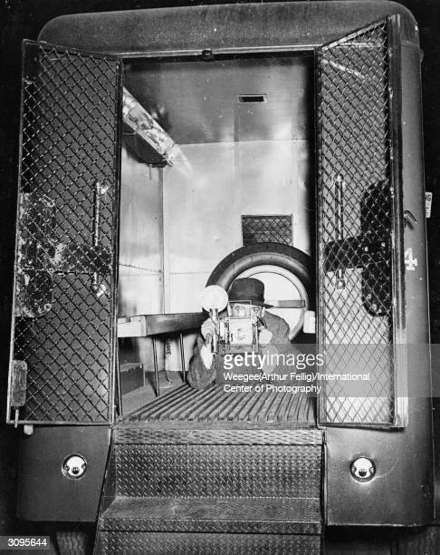 Polish born American photographer Weegee takes a photograph from the interior of a police van Photo by Weegee/International Center of...