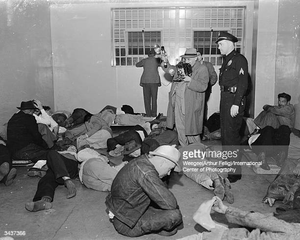 Polish-born American photographer Arthur 'Weegee' Fellig photographing drunks in a 'drunk tank' in New Orleans, Louisiana.