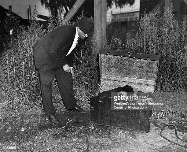 Polishborn newspaper photographer Arthur Fellig better known as Weegee examines a body stuffed into a trunk and deposited on a patch of waste ground...