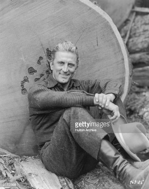 Portrait of American actor Kirk Douglas smiling and sitting with his back against an enormous fallen tree trunk. Douglas is wearing a checkered work...