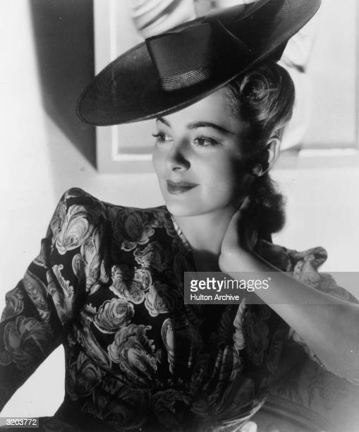 Portrait of American actor Olivia De Havilland smiling while leaning against her elbow in a dress with puffed sleeves and a dark hat