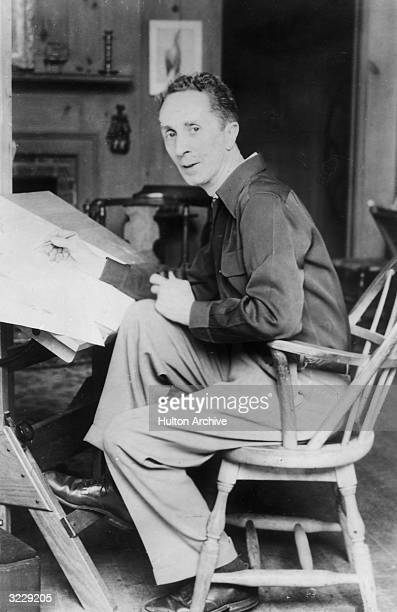 Portrait of American artist Norman Rockwell sketching with a pencil while sitting at a drafting table. He holds a pipe with his free hand.