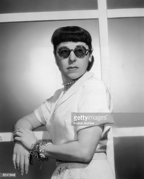 Portrait of American costume designer Edith Head wearing dark glasses and leaning with her arms crossed