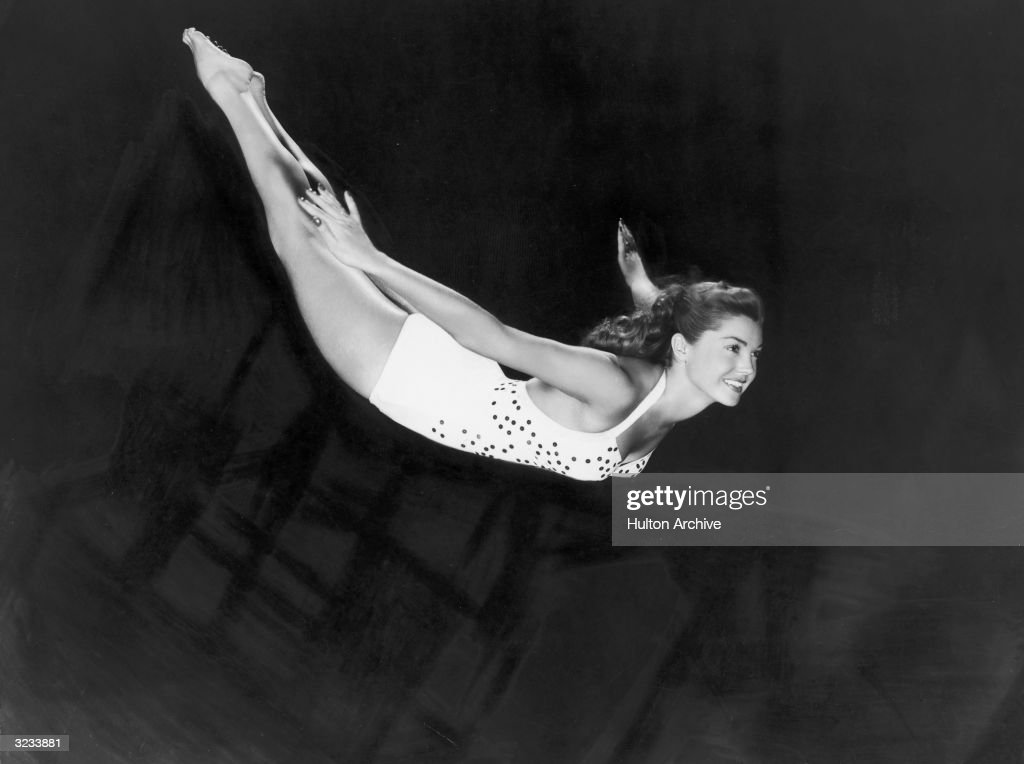Portrait of aquatic American actor and swimmer Esther Williams diving through the air in a one-piece swimsuit.