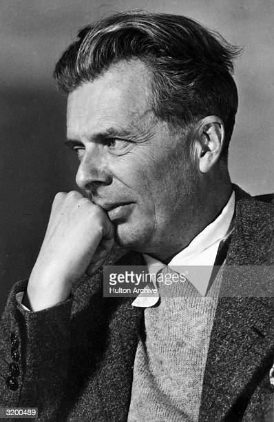 Portrait of British author Aldous Huxley holding a fist up to his face