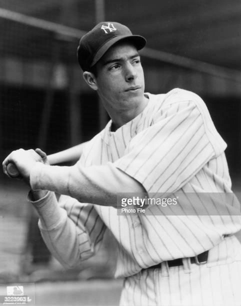 Portrait of New York Yankees outfielder and slugger Joe DiMaggio in his uniform holding a baseball bat
