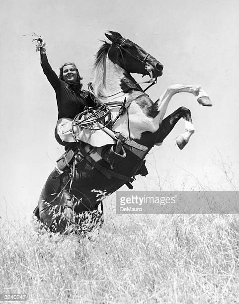 Portrait of rodeo champion and actor Betty Miles riding a bucking horse