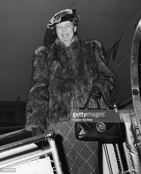 Portrait of US First Lady Eleanor Roosevelt wearing a fur coat and holding a purse smiling while standing on a ramp after exiting an airplane