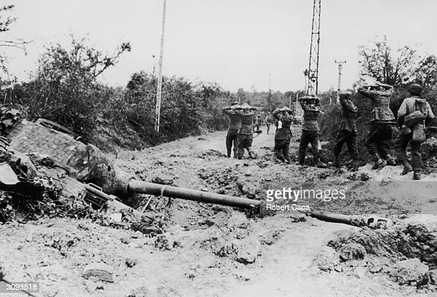 Prisoners being led back past a wrecked German Tiger Tank in the St Lo area of France
