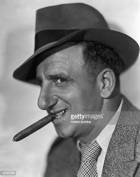 Profile headshot portrait of American actor and comedian Jimmy Durante smoking a cigar and smiling.