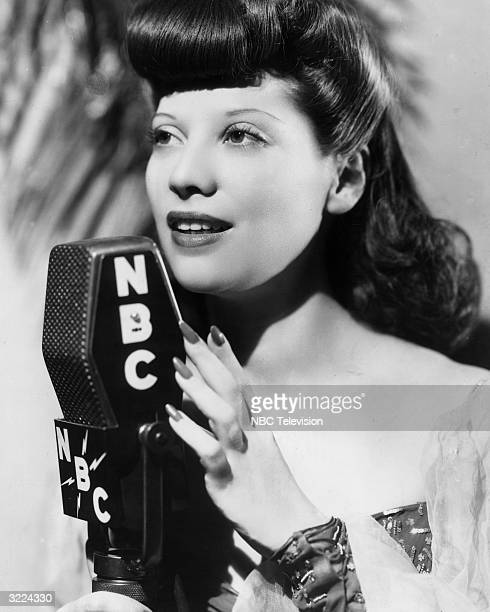 Promotional headshot of American pop singer and actor Dinah Shore standing and singing at an NBC radio microphone 1940s