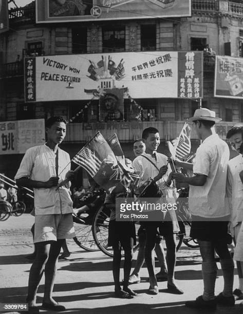 Residents of Shanghai buy flags of the United Nations to celebrate VJ Day when the formal Japanese surrender was signed aboard the US battleship...