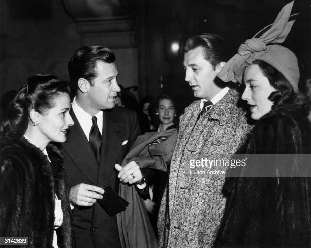 Robert Mitchum and his wife Dorothy Spence chat to Brenda Marshall and her husband William Holden in the El Capitan Theatre lobby before attending...