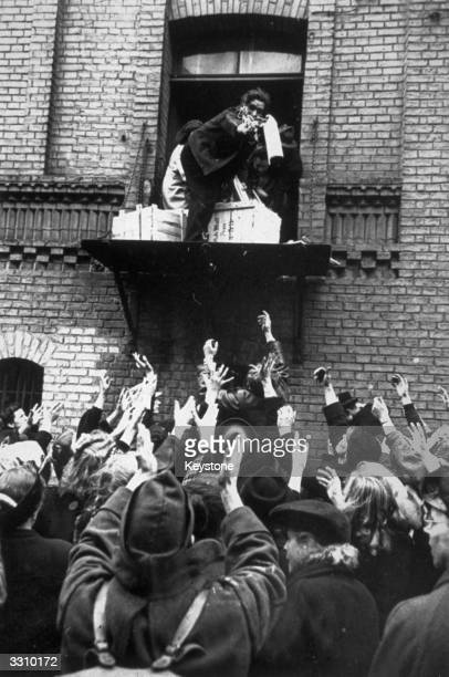 Russian Polish French and German civilians looting a liquor warehouse captured by the Americans Empty bottles are dropped to the mob below in the...