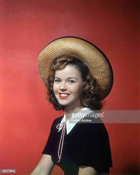 Smiling studio portrait of American actor Shirley Temple sitting in front of a red backdrop wearing a straw hat and black top with white collar