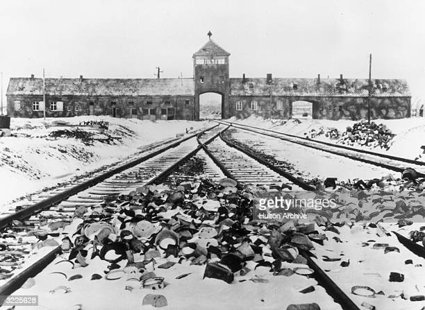 Snow-covered personal effects of those deported to the Auschwitz concentration camp in Poland litter the train tracks leading to the camp's entrance.