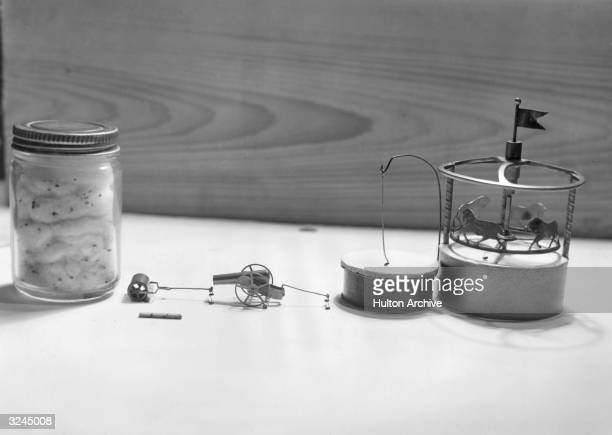 Still life of Professor Ruhl's trained flea circus with fleas pulling a miniature roller and cannon a flea hanging from a hook and a fleapowered...