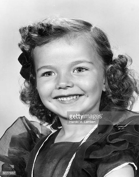 Studio headshot portrait of a young girl with brown curly hair and a puffedsleeve dress smiling