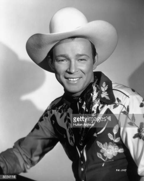 Studio portrait of American actor and country singer Roy Rogers wearing a cowboy hat a western shirt and a scarf tied around his neck
