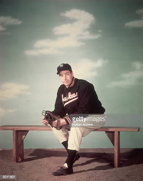 Studio portrait of American baseball player Joe DiMaggio , outfielder for the New York Yankees, sitting on a bench and wearing his uniform in front...