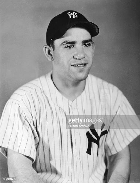 Studio portrait of American baseball player Yogi Berra wearing a New York Yankees uniform and cap