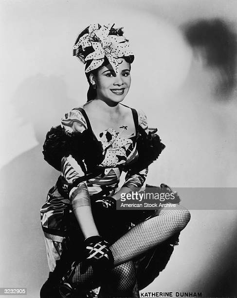 Studio portrait of American dancer and choreographer Katherine Dunham smiling and sitting with her legs crossed Dunham is wearing a dance costume...
