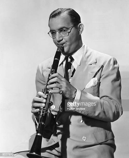 Studio portrait of American jazz musician and bandleader Benny Goodman playing a clarinet in a suit and tie