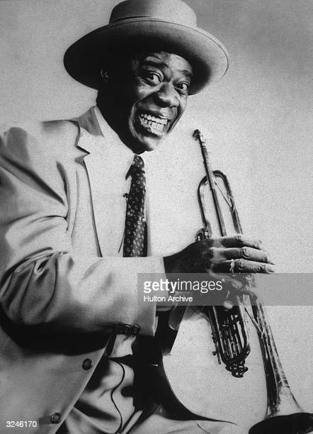 Studio portrait of American jazz musician and bandleader Louis Armstrong grinning and holding his trumpet 1940s