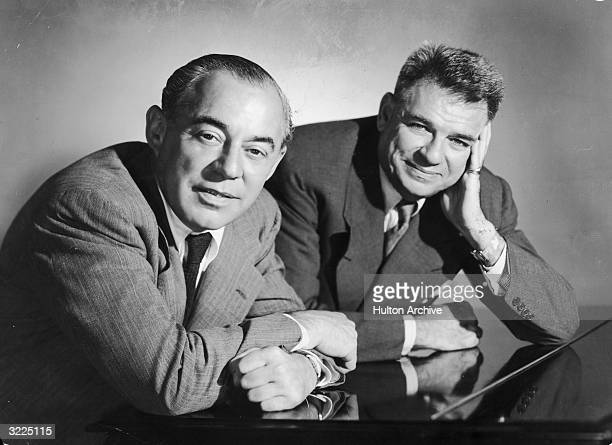 Studio portrait of American musical team composer Richard Rodgers and songwriter Oscar Hammerstein leaning over a piano