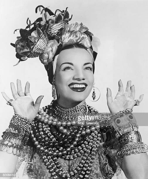 Studio portrait of Brazilian actor Carmen Miranda smiling while posing in a costume with a headdress, bangles, and beaded necklaces.