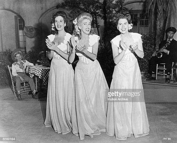 The Andrews Sisters clapping and smiling in matching costumes during a performance