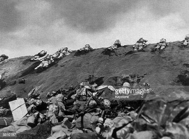 The Fifth Division Marine invaders make their way up the beach of Iwo Jima
