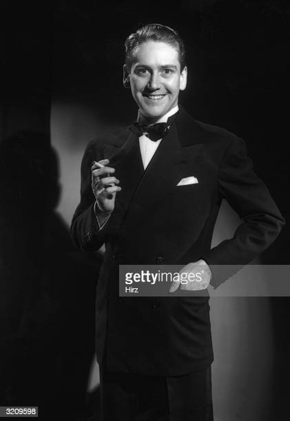 Three-quarter length studio portrait of a man in a tuxedo holding a cigarette and smiling.