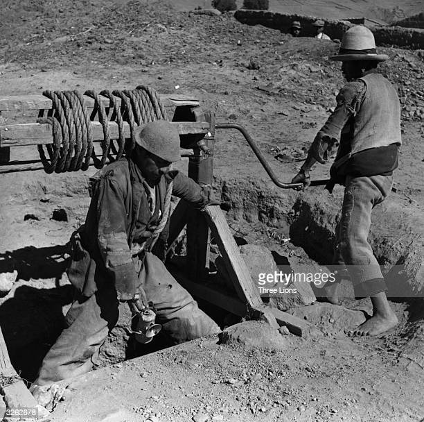 Two men winding up a bucket of ore at a private tin shaft at Llallagua in Bolivia